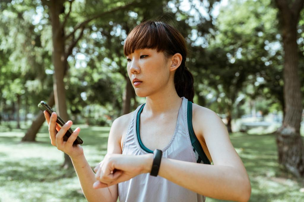 Asian woman tracking her fitness with a phone and wrist tracker  Pandora's Health